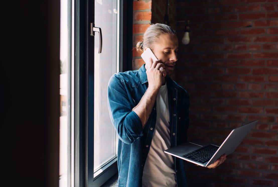 Man som pratar i telefon och håller i laptop